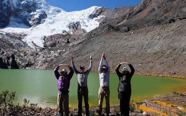 Professors doing OHIO pose in front of mountain and lake